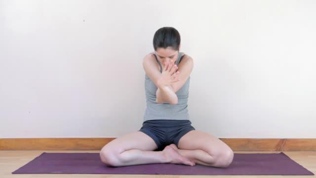 woman doing yoga - auf dem boden sitzen stock-videos und b-roll-filmmaterial