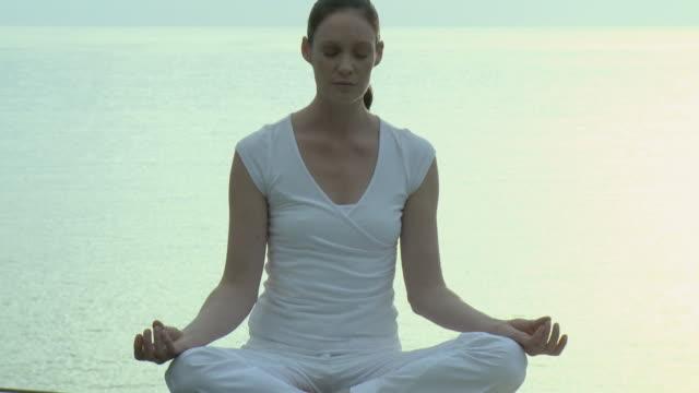 ms woman doing yoga with sea in background / cape town, south africa - korslagda ben bildbanksvideor och videomaterial från bakom kulisserna