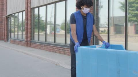 stockvideo's en b-roll-footage met de vrouw schenkt gebruikte kleding - shopping centre