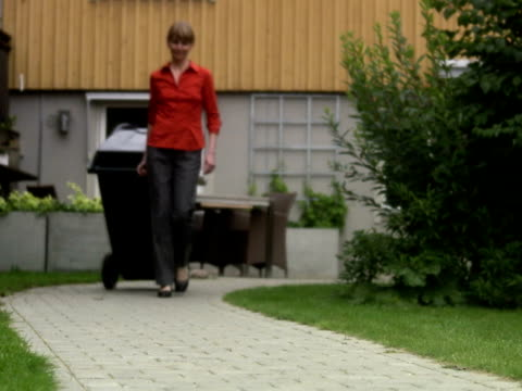 vídeos y material grabado en eventos de stock de a woman dragging a dustbin from a house sweden. - contenedor para la basura