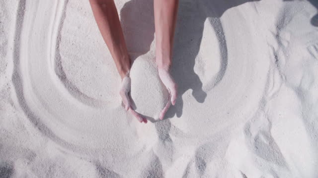 a woman drawing a heart in the sand at the beach. - valentine's day stock videos & royalty-free footage