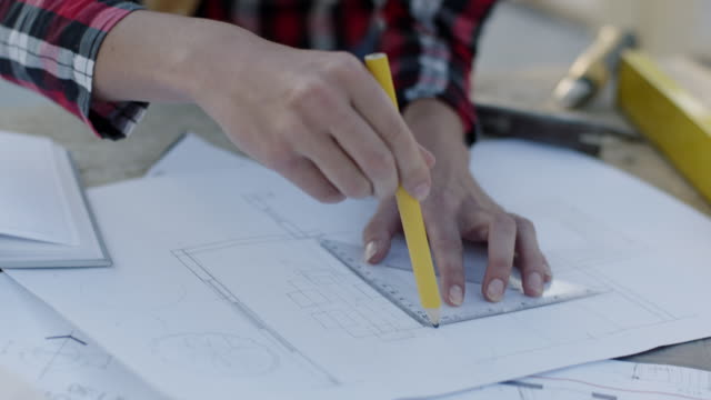 Woman drawing building plans at construction site