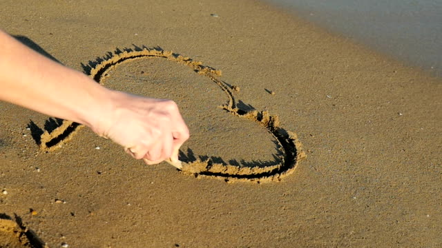 Woman drawing heart shape in sand