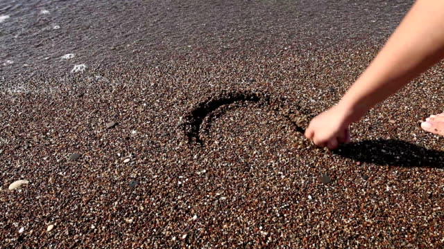 woman drawing heart shape in sand - approaching stock videos & royalty-free footage