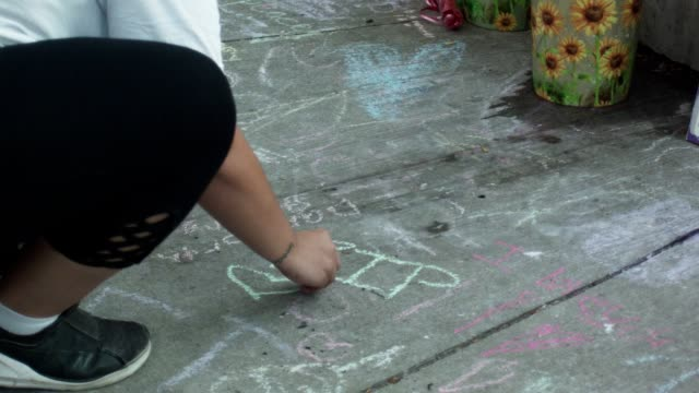 a woman draws a heart with chalk at the greektown vigil - violence stock videos & royalty-free footage