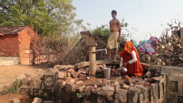 a woman draws water from a communal water pump in the village of lar sauryana in tikamgarh madhya pradesh india on friday feb 8 women and children... - madhya pradesh stock videos and b-roll footage