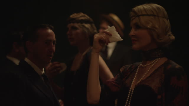 a woman dressed as a 1920's flapper waves a handkerchief in front of her face while others watch. - kostümierung stock-videos und b-roll-filmmaterial