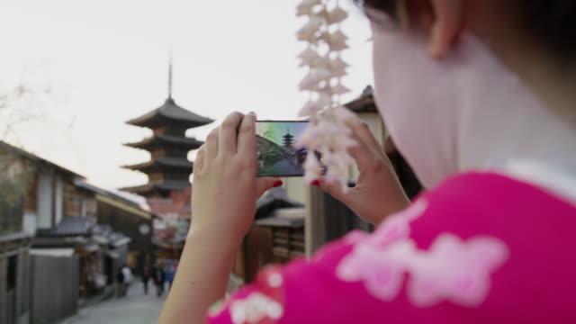vídeos y material grabado en eventos de stock de ms a woman dressed as a maiko takes photographs on a phone / kyoto, japan - esmalte de uñas rojo