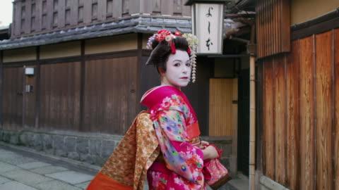 ms a woman dressed as a maiko walks through kyoto / kyoto, japan - tradition bildbanksvideor och videomaterial från bakom kulisserna