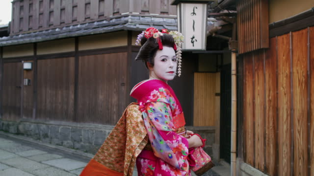 ms a woman dressed as a maiko walks through kyoto / kyoto, japan - över axel perspektiv bildbanksvideor och videomaterial från bakom kulisserna