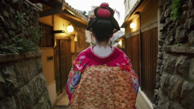 ms a woman dressed as a maiko walks through kyoto / kyoto, japan - giappone video stock e b–roll