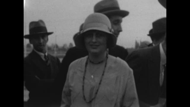 A woman dressed as aflapper poses for the camera while men in hats ans suits talk in the background at Carnival in Buenes Aires 1927.