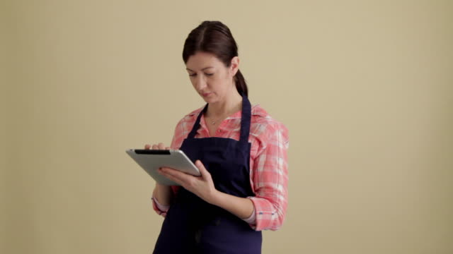 mws woman dressed as grocer using tablet looking up and smiling to  to camera - lebensmittelhändler stock-videos und b-roll-filmmaterial