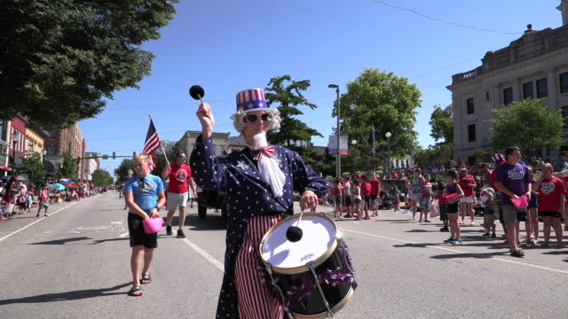a woman dressed as uncle sam bangs a drum while marching as part of the southern indiana pipes drums during the 4th of july parade thursday july 4... - uncle sam stock videos & royalty-free footage