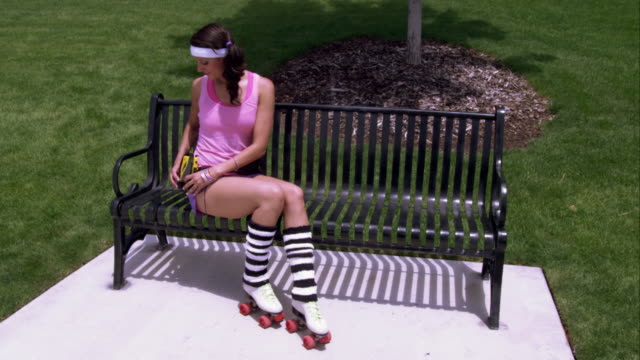 woman dressed in 80's athletic clothing and roller skates gets up from the bench in the park. - knee highs stock videos and b-roll footage