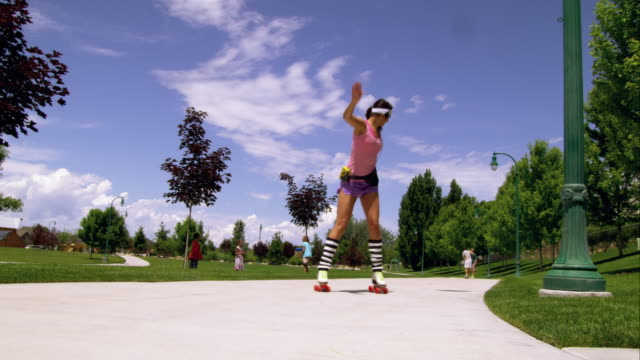 woman dressed in 80's athletic clothing roller skating in the park. - personal stereo stock videos & royalty-free footage