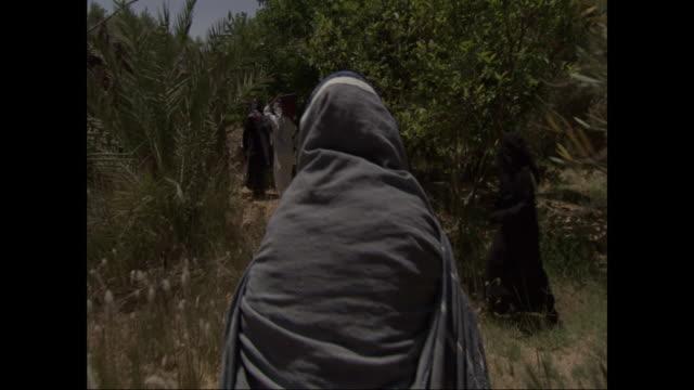 a woman dressed in a burka walks down a dusty path behind several other people. - モデスト・ファッション点の映像素材/bロール