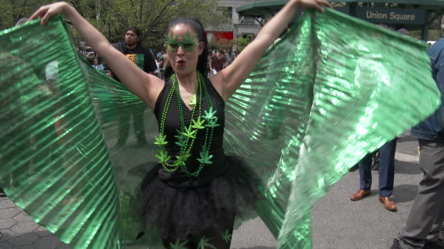 A woman dressed in a Marijuana themed costume dances for the camera at the Cannabis Day Rally in Union Square Park New York