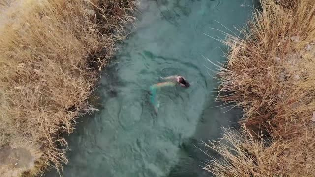 woman dressed in a mermaid costume was filmed serenely swimming through a utah river fed by warm springs on december 20, 2020. vivian beck, the... - swimming costume stock videos & royalty-free footage
