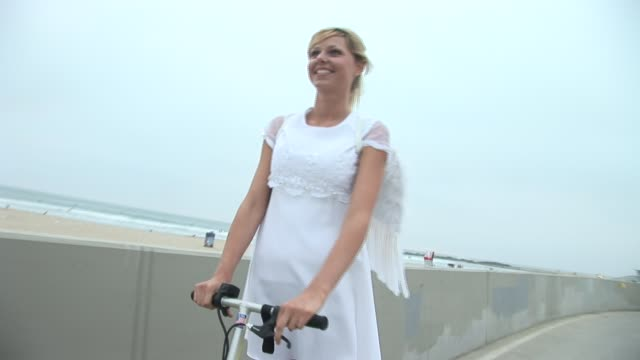 ms ts woman dressed in angel costume riding motor scooter/ venice beach, california - eccentric stock videos and b-roll footage