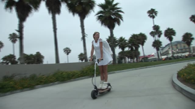 ws woman dressed in angel costume riding motor scooter/ venice beach, california - pferdeschwanz stock-videos und b-roll-filmmaterial