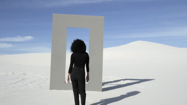 woman dressed in black walks through doorframe in desert, wide - frizzy hair stock videos and b-roll footage