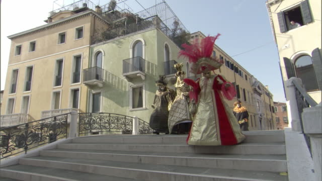 ws pan woman dressed in lavish costume for venice carnevale wearing painted mask and feathered head-dress / venice, veneto, italy - headdress stock videos & royalty-free footage