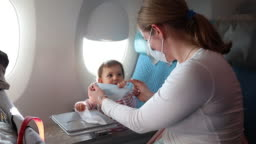 woman dresses in a protective face gauze bandage on an airplane. Trying to put on a mask on a child. He resists. Protection against corona virus, respiratory infections flu. Fighting covid 19