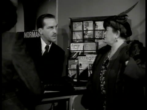 vidéos et rushes de woman dresses in coat fur shoulder wrap talking to man in travel agency sot saying everything's booked could go on american ship woman saying nobody... - 1935