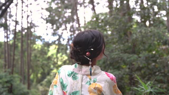 woman dressing a kimono or yukata in a japanese forest - yukata video stock e b–roll