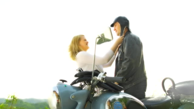 hd slow motion: woman dressing her man - moped stock videos and b-roll footage