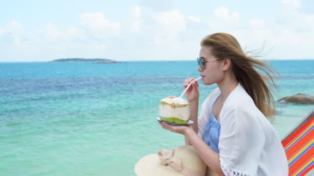 vídeos y material grabado en eventos de stock de mujer beber un agua de coco en silla cómoda en la playa, espacio de copia. - cóctel tropical