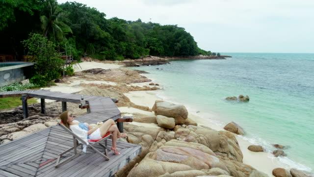 stockvideo's en b-roll-footage met vrouw drink een kokosnoot water op comfortabele stoel op het strand neergeschoten door drone. - tropische drankjes