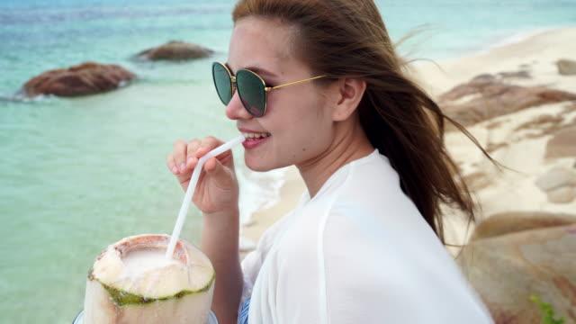 stockvideo's en b-roll-footage met vrouw drink een kokosnoot water op comfortabele stoel op het strand. - tropische drankjes