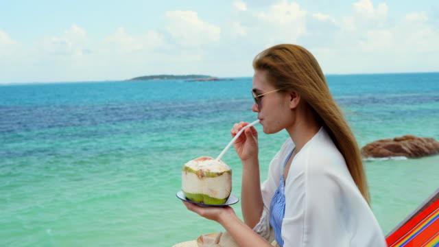 vídeos y material grabado en eventos de stock de mujer beber un agua de coco en silla cómoda en la playa - cóctel tropical