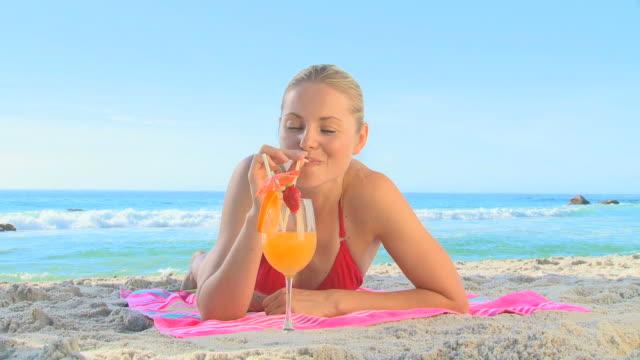 vídeos y material grabado en eventos de stock de  woman drinking a cocktail on a beach / cape town, western cape, south africa - tumbado boca abajo