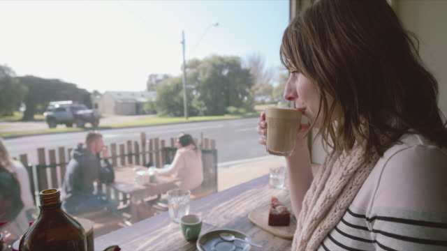 A woman drinking a coffee and smiling at Mornington Peninsula, Victoria, Australia