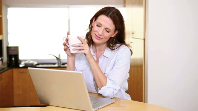 woman drinking a coffee in front of her laptop - einzelne frau über 30 stock-videos und b-roll-filmmaterial