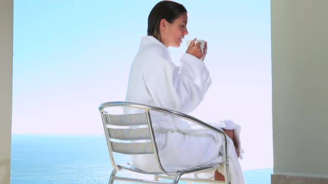 woman drinking a coffee with a sea view - bathrobe stock videos & royalty-free footage