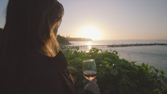 a woman drinking a glass of wine at sunset, mornington peninsula, victoria, australia - refreshment stock videos and b-roll footage