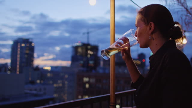 Woman Drinking and Smoking on Rooftop Terrace