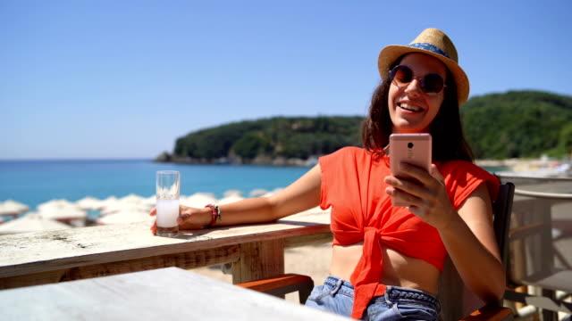 frau trinkt und textet auf der strandterrasse - junge frau allein stock-videos und b-roll-filmmaterial