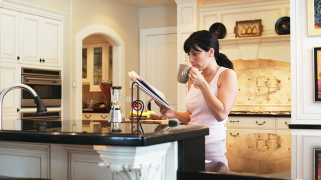 woman drinking coffee and reading in the kitchen