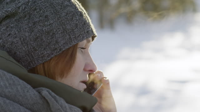 Woman drinking coffee and talking on phone outside in winter