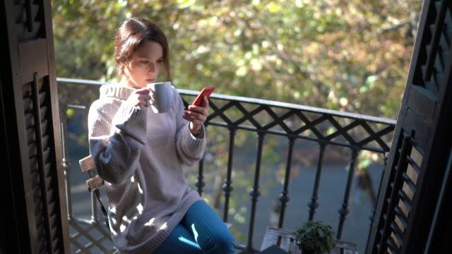 vidéos et rushes de femme buvant le café et textant à la terrasse - balcon