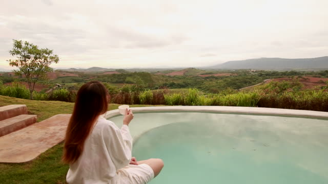 hd dolly: woman drinking coffee by the pool - hot tub stock videos and b-roll footage