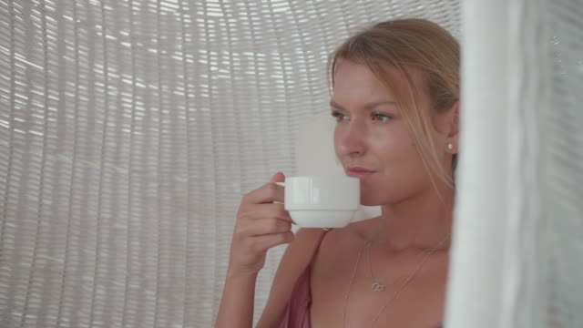a woman drinking coffee espresso in the morning at a resort hotel. - espresso stock videos & royalty-free footage