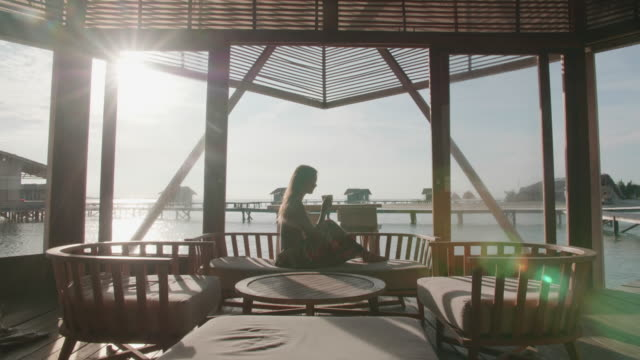 a woman drinking coffee espresso in the morning at a tropical island hotel resort. - パレオ点の映像素材/bロール