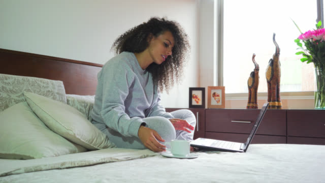 woman drinking coffee in bed in the morning and typing on a laptop