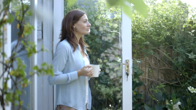 Woman drinking coffee outside home.